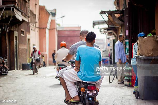 CONTENT] A common street in Marrakesh as mopeds with up to 2 or 3 people get about the Red City on two wheels