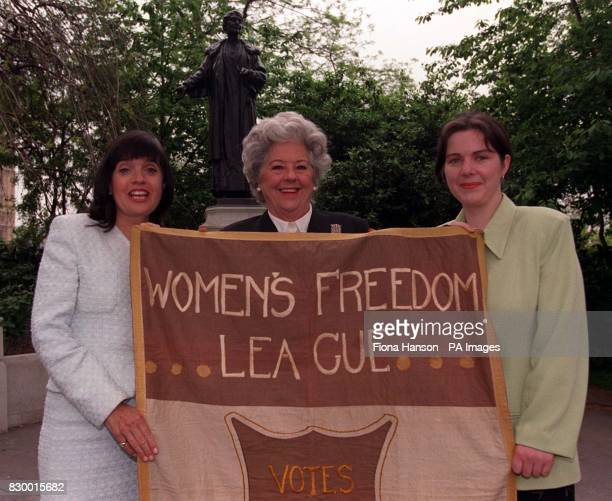 Commons speaker Betty Boothroyd flanked by MP Barbara Follett Founder of Emily's List and MP Claire Ward hold an original 1908 Suffrage banner saying...