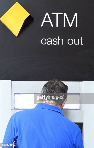 A Commonwealth bank customer uses an automated teller machine outside a bank branch in central business district of Sydney on September 21 2017...
