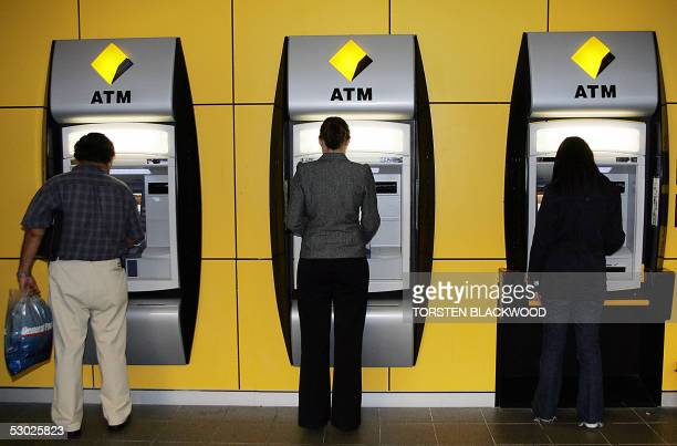 Commonwealth Bank customers use automatic teller machines in Sydney 06 June 2005 as the Reserve Bank of India announced the approval for the...
