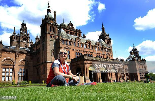 Commonwealth games Volunteer Jane Whitaker sits on the grass outside Kelvingrove Museum and Art Gallery next to the Lawn Bowls arena in Kelvingrove...