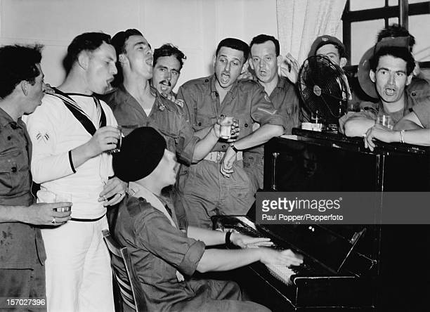 Commonwealth servicemen on leave during the Korean War singing round a piano at the Ebisu Hostel Tokyo Japan 1950