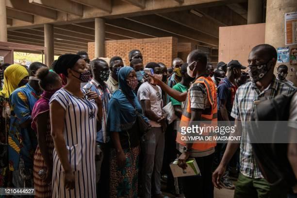 Communal agent measures the body temperature of traders at the opening of Rood Wokos great market in Ouagadougou on April 20 after the market was...
