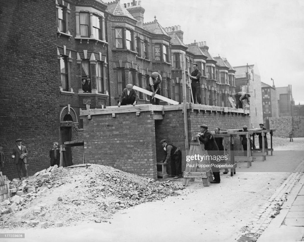 Communal air raid shelters under construction in a south London street at the outbreak of World War II, 2nd October 1939. The shelters are brick with rooves of reinforced concrete, and are being provided for residents without the space for shelters of their own.