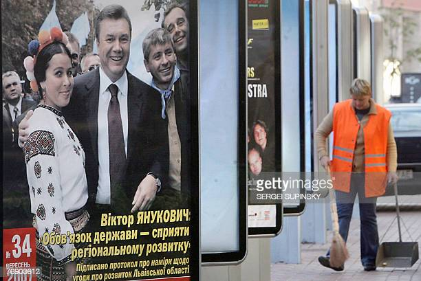 Communal service worker cleans around billboards of the pre-election ads for the pro-Russian Regions party of Prime minister Viktor Yanukovich 20...