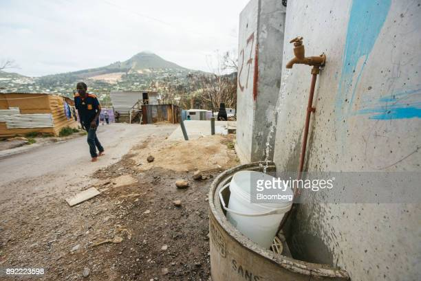 A communal water taps runs to fill a plastic container underneath in the Imizamo Yethu township outside Cape Town South Africa on Monday Nov 13 2017...