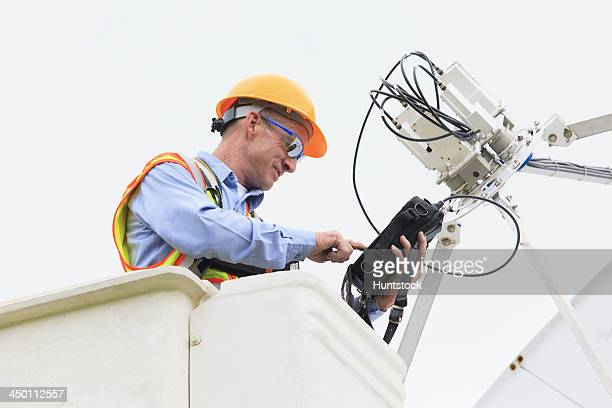Communications engineer measuring signal level at low noise amplifiers and feedhorns at satellite dish