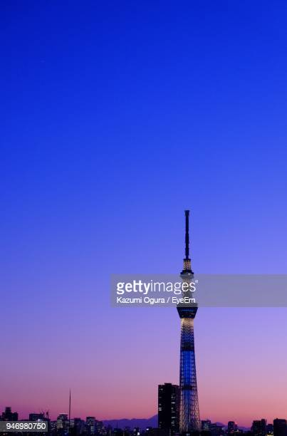 Communications Tower In City Against Blue Sky