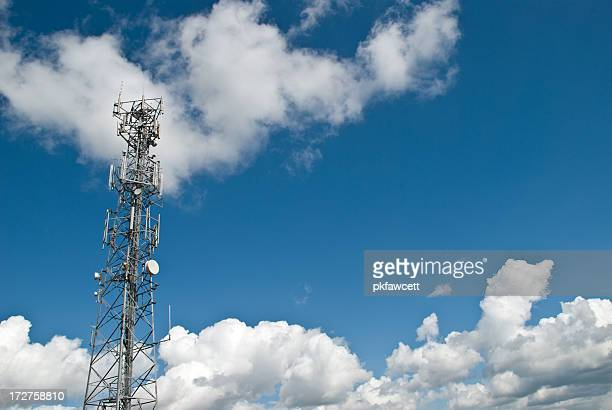Communications tower with cloudy sky background