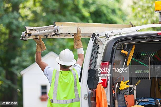 Communications worker loading a ladder onto a truck