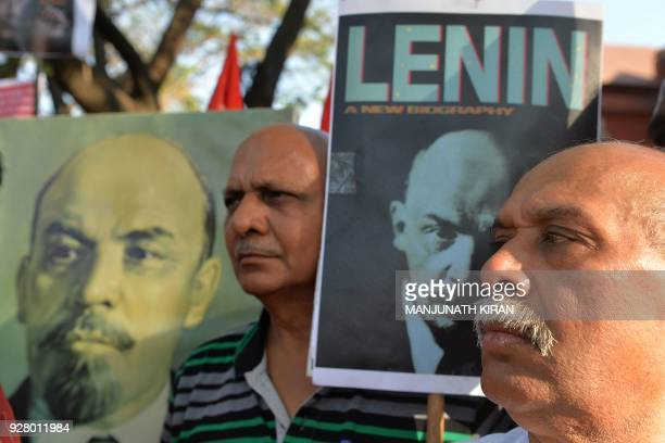 Communist activists of the Socialist Unity Centre of India look on nex to posters of communist leader Vladimir Lenin during a protest demonstration...