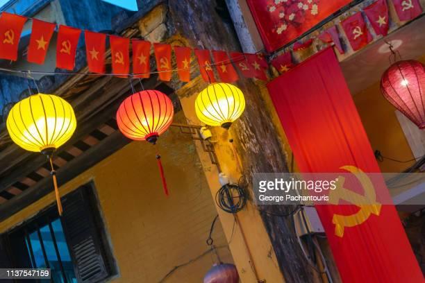communist and vietnamese flag among paper lanterns - bandiera comunista foto e immagini stock