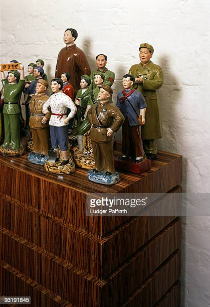 communist ceramic figurines arranged on a wooden cabinet - mao tsé toung stockfoto's en -beelden