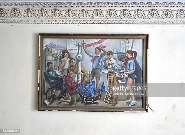 A Communist era painting depicting pioneers making model airplanes hangs at the Culture House in Horesti south of the capital on October 25 2016 /...