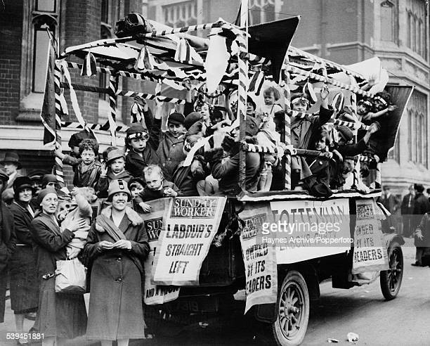 A Communist float covered with fliers from the Sunday Worker and the Tottenham Labour Party during a May Day parade and the Feast of Oratory in Hyde...