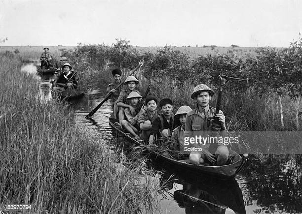 Communist guerrillas travel in small boats through a swamp under cover of reeds on thir way to making a surprise attack on US forces in Dong Thap...