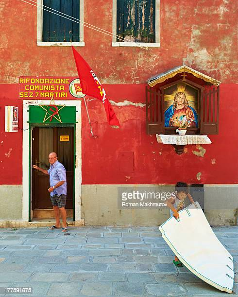 CONTENT] Communist headquarters next to the Catholic point with Jesus Christ painting Boy drags construction piece nearby Old man walking out of the...