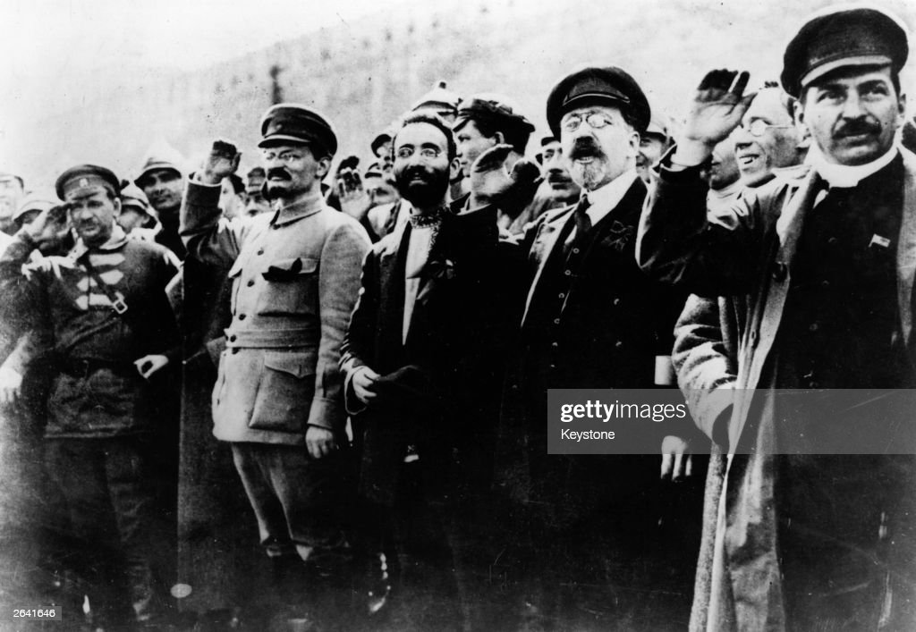 Communist leaders including Joseph Stalin (1879 - 1953) and Leon Trotsky (1879 - 1940) seen saluting in the street during the Russian Revolution.