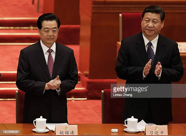 Communist Party chief Xi Jinping and Chinese President Hu Jintao applaud during the opening session of The Chinese People's Political Consultative...