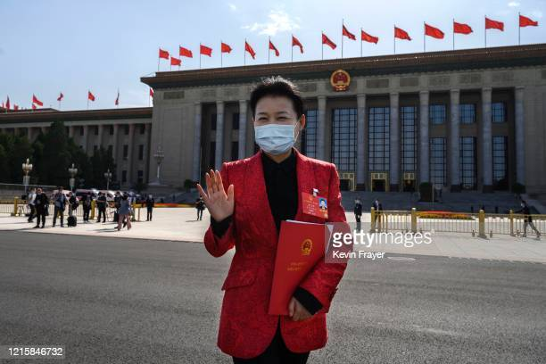 Communist Party delegate wears a protective mask as she gestures while leaving after the closing session of the National People's Congress at the...