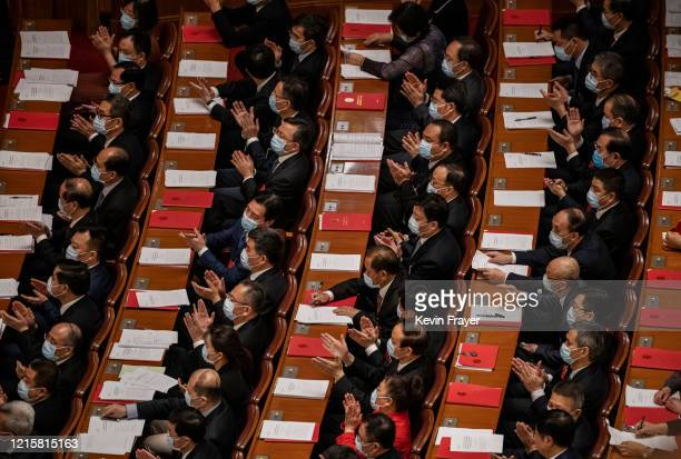 Communist Party delegates applaud during the closing session of the National People's Congress which included a vote on a new draft security bill for...