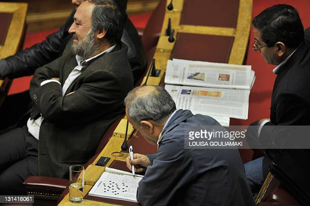 Communist party deputies look on as one plays word games during a debate on the confidence vote at the Greek Parliament in Athens on November 4,...