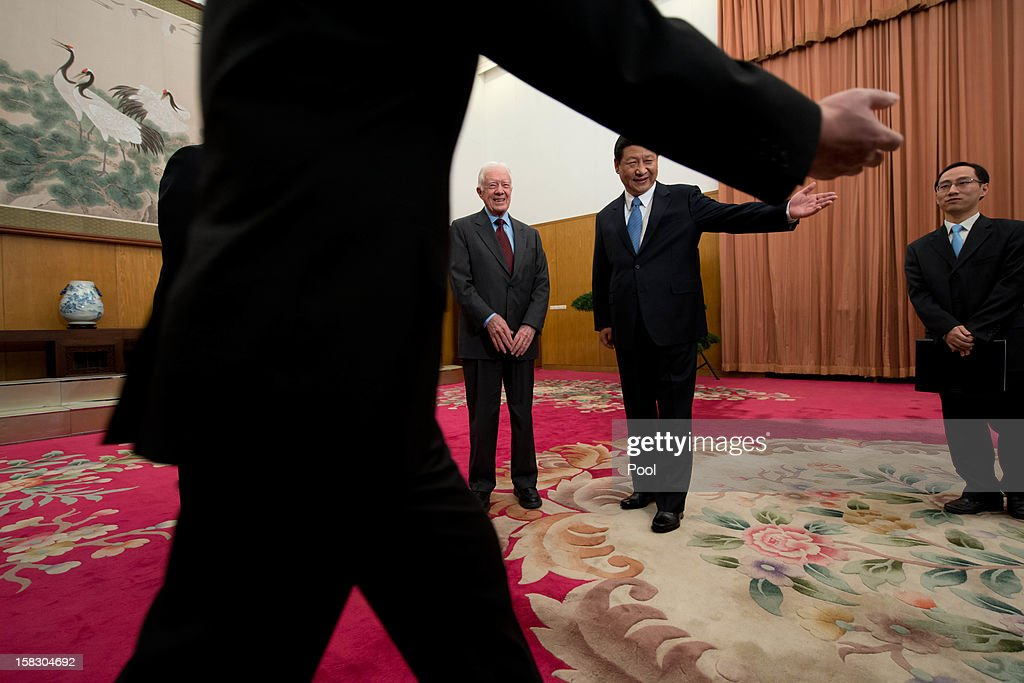 Communist Party leader Xi Jinping (R) gestures with former US President Jimmy Carter (L) in room 202 of the Zhongnanhai leadership compound on December 13, 2012 in Beijing, China. Carter congratulated Xi on his new position before the pair sat down for talks.