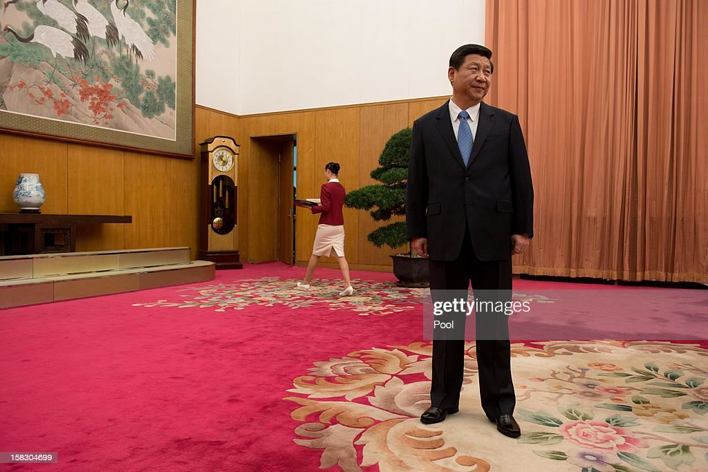 Communist Party leader Xi Jinping (C) waits to greet former US President Jimmy Carter in room 202 of the Zhongnanhai leadership compound on December 13, 2012 in Beijing, China. Carter congratulated Xi on his new position before the pair sat down for talks.