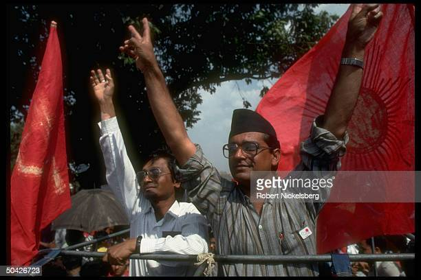 Communist Party of Nepal General Secretary Madan Bhandari veeing fingers on stump framed by CPM UML red flags candidate in first free election in 30...