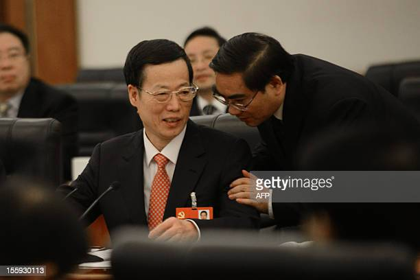 Communist Party Secretary of Tianjin, Zhang Gaoli, talks with a delegate as he attends a panel discussion of the Tianjin delegation during the18th...