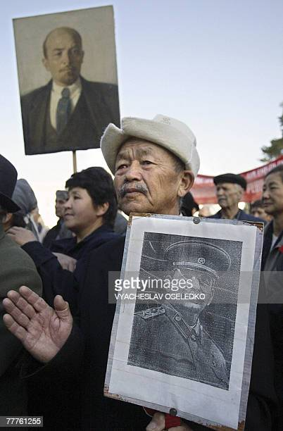 Communist party supporters hold pictures of Soviet leaders Vladimir Lenin and Josef Stalin during a rally marking the 90th anniversary of the October...