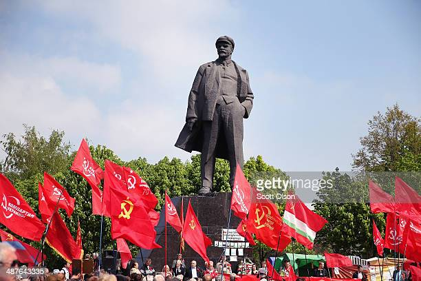 Communist party supporters march past a statue of Vladimir Lenin as they arrive for a May Day rally in Lenin Square on May 1 2014 in Donetsk Ukraine...