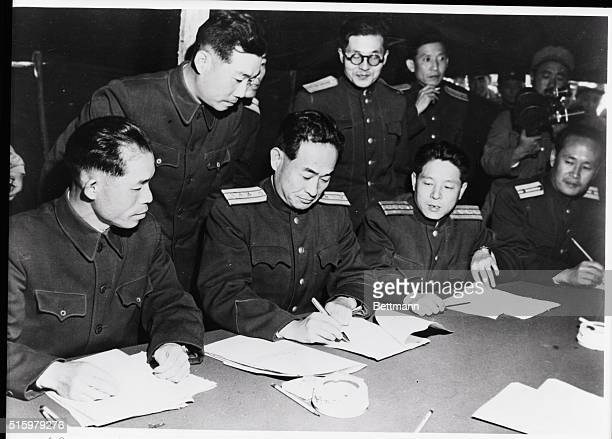 Communist representatives sign the agreement for the neutral zone, reached through negotiations with United States military representatives during...