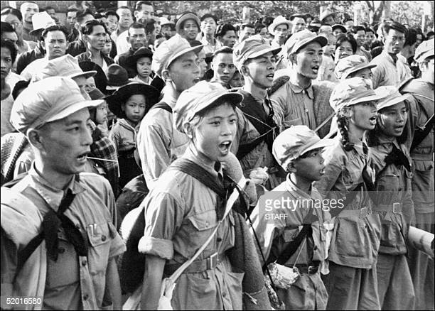 Communist soldiers from the East river unit, with among them several women, song an hymn to Mao Tse Tung glory as they arrive in Sham Chum, three...