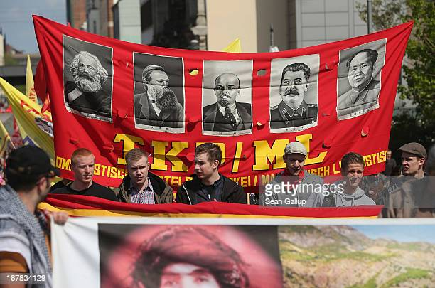 Communist supporters march bearing portraits of Marx Engels Lenin Stalin and Mao as they join labour union representatives and other groups...