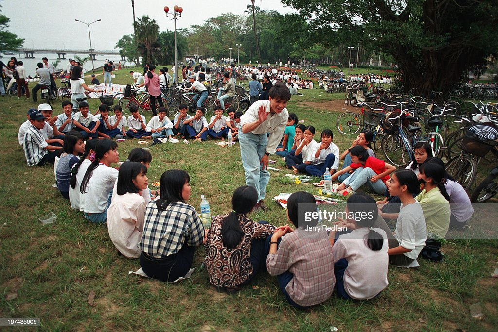 Communist youth groups from local schools gather for meetings along the riverside in Hue. Evenings bring crowds of people to the riverside to cool off during the hot season..