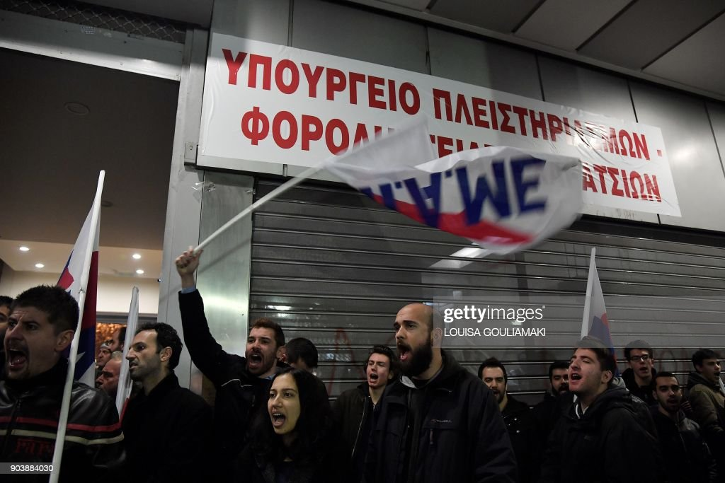 Communist-affiliated All-Workers Militant Front (PAME) unionists chant slogans after setting up a banner reading 'Ministry of foreclosures and tax thieves' at the Greek Finance Ministry in Athens on January 11, 2018, during a protest against a law submited to the parliament which includes strike restrictions as part of the Greek austerity measures. Workers call for a strike on January 12 and brace for protests as another round of austerity measures is debated in Parliament this week. /