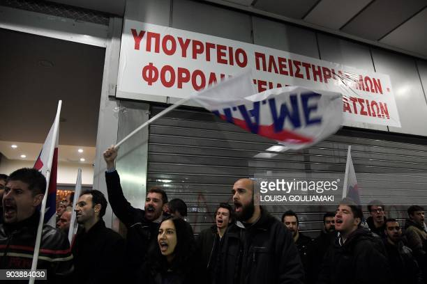 Communistaffiliated AllWorkers Militant Front unionists chant slogans after setting up a banner reading 'Ministry of foreclosures and tax thieves' at...