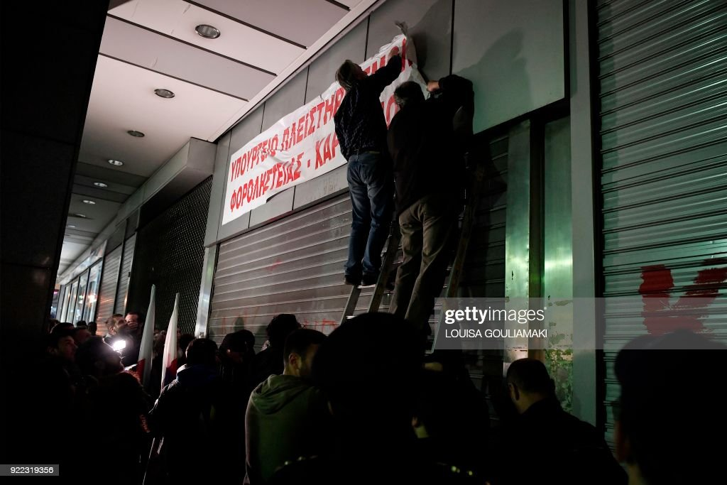 Communist-affiliated All-Workers Militant Front (PAME) unionists set up a banner reading 'Ministry of foreclosures and tax thieves' at the Greek Finance Ministry in Athens on February 21, 2018 during a protest against property auctions demanded by Greece's creditors as part of the Greek austerity measures. /