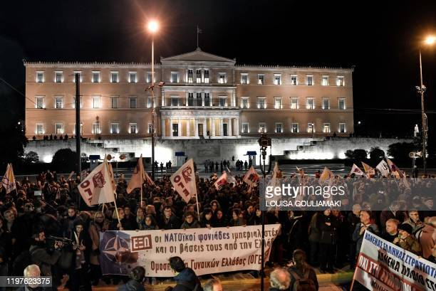 Communist-affiliated and leftist protesters hold an anti-NATO rally outside the Greek Parliament in Athens on January 30, 2020 while the parliament...