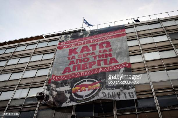Communistaffiliated PAME workers unionists hang a banner after storming the Ministry of Labour in Athens on January 9 2018 during a protest against a...