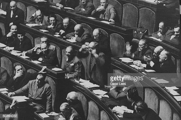 Communists in Senate jeer premier Mario Scelba showing rows of seated delegates applauding heckler president of Senate calling for order while Scelba...