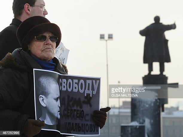 A Communists supporter holds a poster reading 'Free Sergei Udaltsov' with his portrait during an action in support of the ultraleft opposition leader...