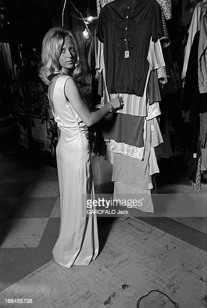 Communities In California EtatsUnis Californie janvier 1971 ici dans une boutique de mode une femme est debout devant des teeshirts sur cintres...