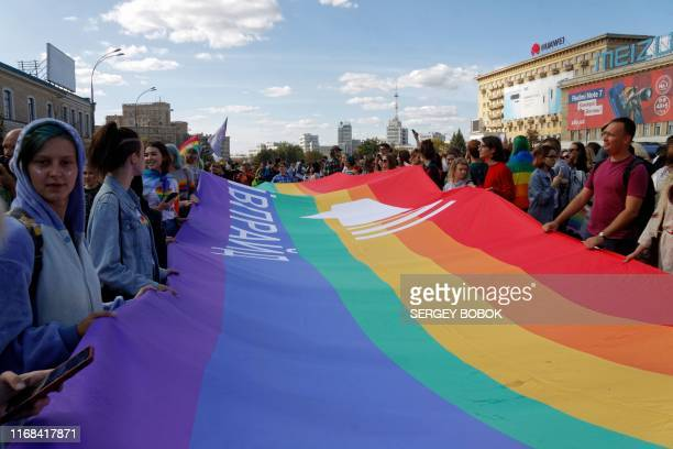 LGBT community activists hold a giant Rainbow flag during the Kharkiv Pride march in Kharkiv on September 15 2019