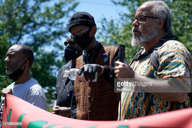 Community elders pour libation to reclaim the grounds after a statue of Christopher Columbus was removed as hundreds participate in a rally organized...