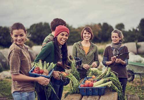 Community farming peers standing together with the allotment produce, laughing - gettyimageskorea