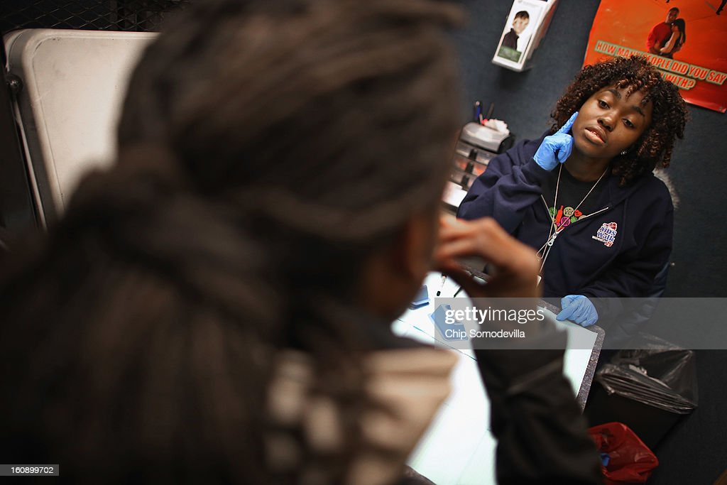 Community Health Educator Nanah Fofanah guides a young man through an oral HIV test inside the Whitman-Walker Health mobile testing site as part of National Black HIV/AIDS Awareness Day February 7, 2013 in Washington, DC. The HIV prevalence rate in the District of Columbia is at an epidemic level at nearly 3 percent, among the highest for any U.S. city, with nearly 15,000 adults in the district living with HIV or AIDS.