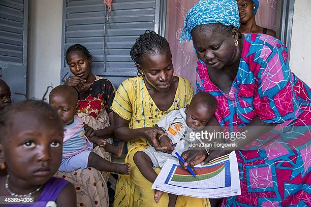 A community health worker providing women in her community counseling and post natal care at her home The women are also given counseling about...