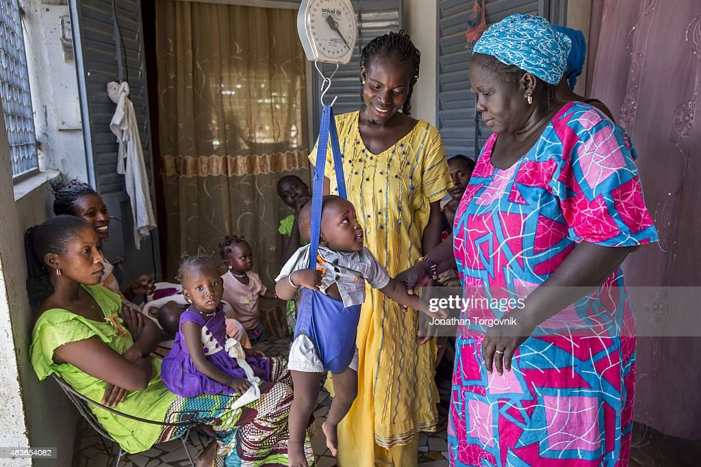 A community health worker providing women in her community counseling and post natal care at her home. The women are also given counseling about reproductive health issues and family planning. August 20, 2014 in Kaolack, Senegal.